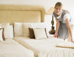 Female maid cleaning hotel room with towels in hand