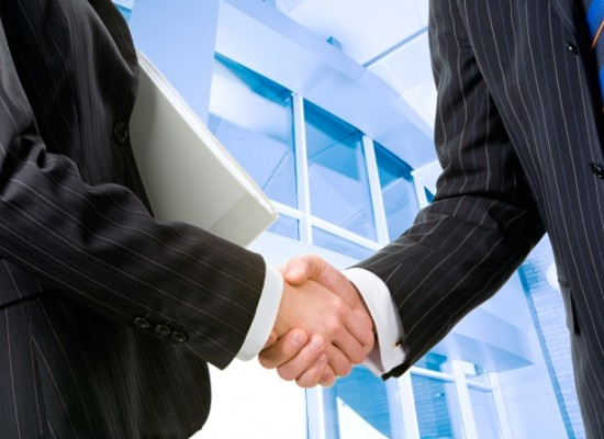 Two partners shaking hands at meeting in front of building