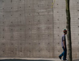A man passes by in front of a wall at Piccadilly Gardens, Manchester.