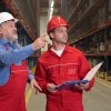 two workers in uniforms in warehouse counting stocks