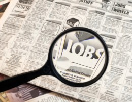 newspaper opened to the want ads.  magnifying glass highlighting the word jobs.
