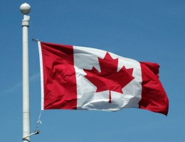 A Canadian flag in blue sky background