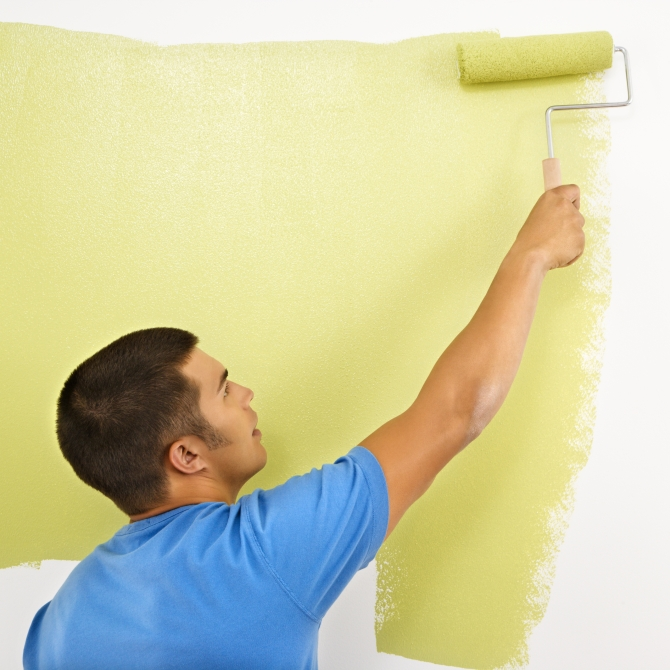 Man painting over white wall with green paint using paint roller.