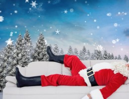 Santa claus sleeping on the couch against snowy landscape with fir trees