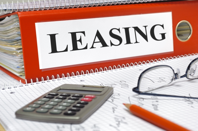 leasing contracts in folder with calculator and red pencil