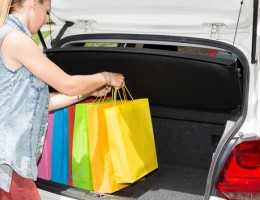 Young woman putting the groceries in the trunk of her car