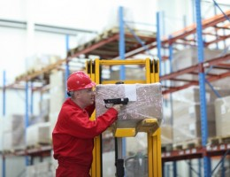 Worker with bar code reader working in warehouse - close up