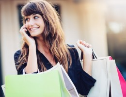 Happy woman holding shopping bags smiling and holding cell phone