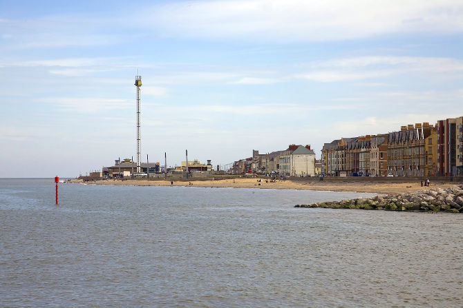 River Clwyd meets Irish sea at Rhyl harbour in north Wales, UK. With disused tourist attraction skytower in the background.