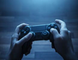 Close up of child hands playing the video game late at night