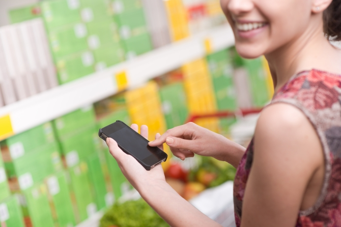 Smiling young woman at supermarket using mobile phone and looking at camera.